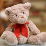 selective focus photo of brown teddy bear with red bow