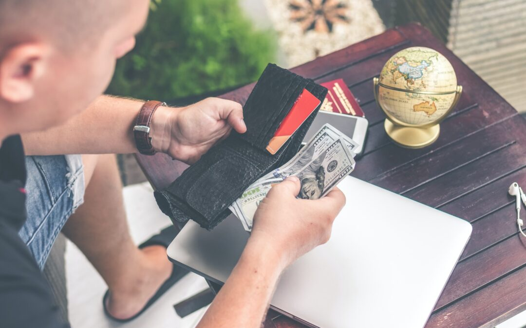 person holding wallet and US dollar bills